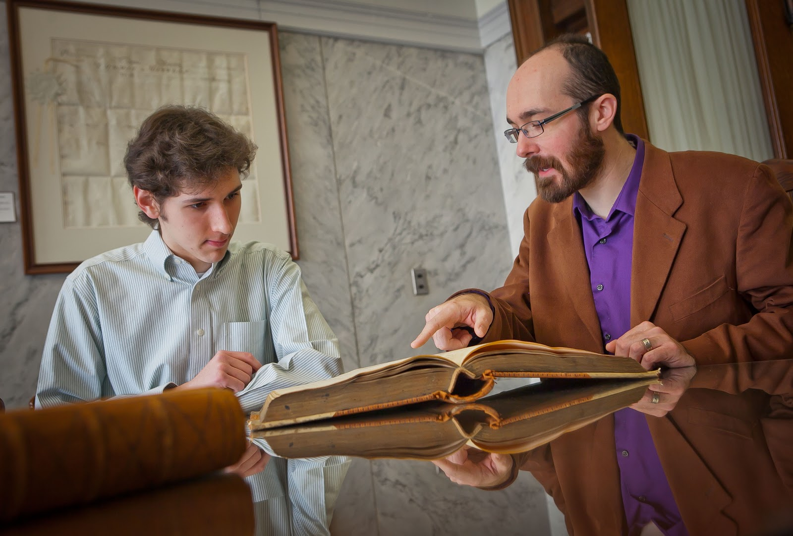 image of professor phillips opening a book and pointing to something with a student